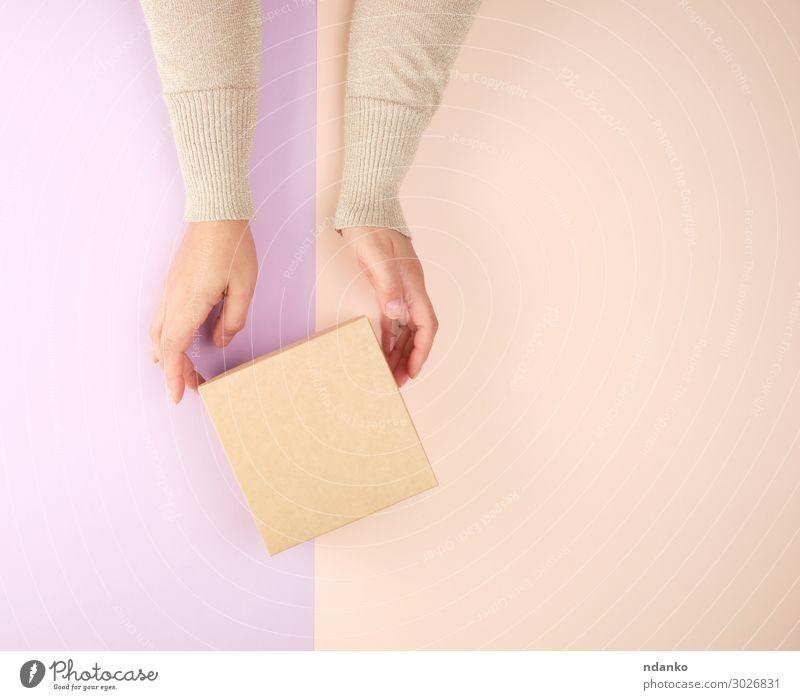 Mädchen hält eine braune, quadratische Schachtel. Dekoration & Verzierung Feste & Feiern Hochzeit Geburtstag Frau Erwachsene Hand Papier Paket Herz festhalten