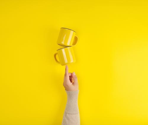 zwei gelbe Keramikbecher werden von einer weiblichen Hand getragen. Frühstück Kaffee Tee Tasse Küche Arme Finger heiß hell Sauberkeit Farbe abstützen Halt