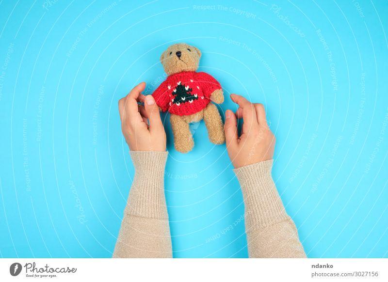 zwei weibliche Hände halten einen kleinen Spielzeugteddybären. Freude Körper Kind Kindheit Hand Tier Puppe Teddybär Spielen lustig niedlich retro weich blau