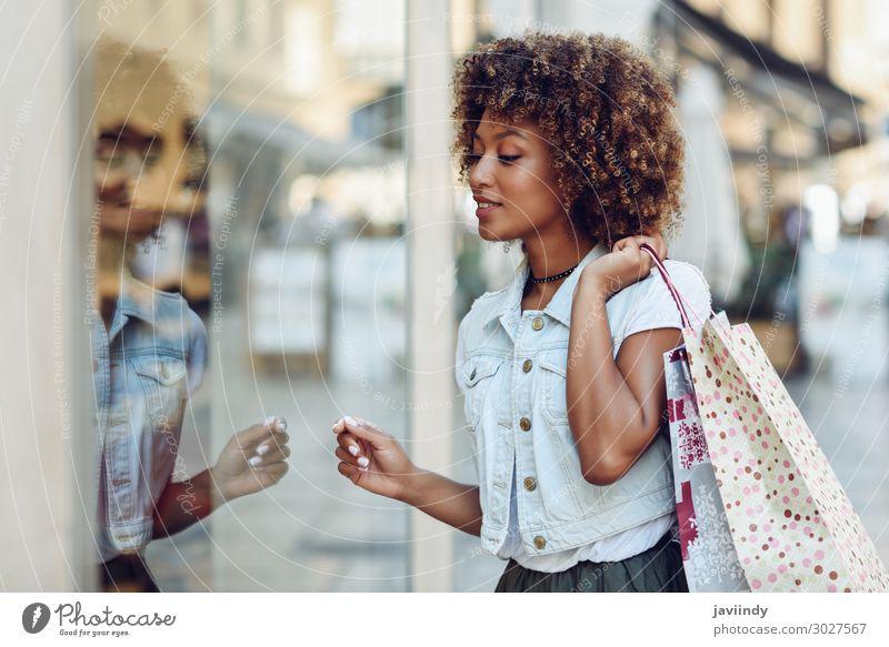 Junge schwarze Frau vor einem Schaufenster in einer Einkaufsstraße. Lifestyle kaufen Stil Glück schön Haare & Frisuren Mensch feminin Junge Frau Jugendliche