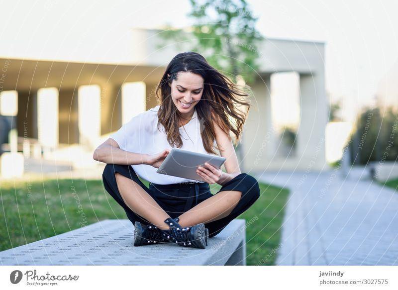 Junge Frau, die ein digitales Tablet benutzt und im städtischen Hintergrund im Freien sitzt. Lifestyle Glück schön lesen Studium Arbeit & Erwerbstätigkeit Beruf
