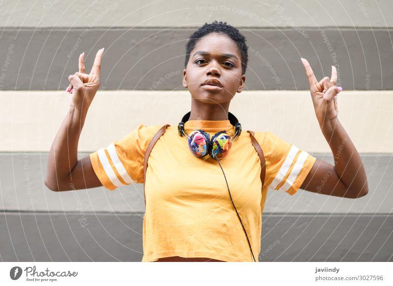Schwarze Frau, die die Geste der Hörner macht. Stil Haare & Frisuren Gesicht Musik Headset Mensch feminin Junge Frau Jugendliche Erwachsene Hand Finger 1