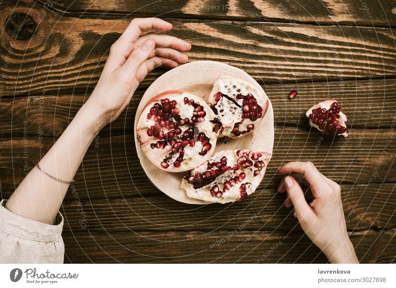 Frauenhände und ein Teller mit Granatapfel auf Holztisch Tisch Vegetarische Ernährung organisch süß Gesundheit Gesunde Ernährung flache Verlegung Lebensmittel