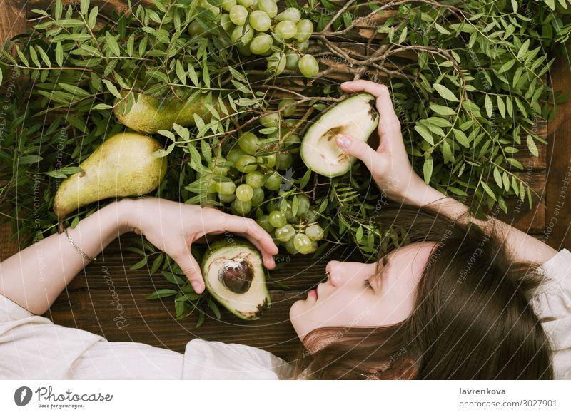 Frau, die auf einem Holztisch liegt und Trauben, Birnen und Avocados hält. Landwirtschaft Ackerbau Ast Bauernhof flache Verlegung Lebensmittel Gesunde Ernährung