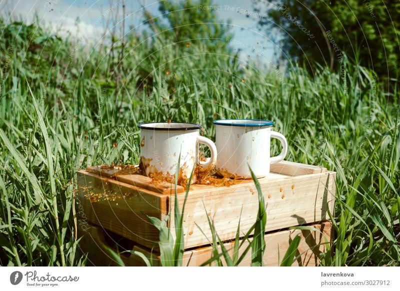 Emailbecher mit Kaffee oder Tee auf einer Holzkiste Frühling Gras Außenaufnahme Getränk trinken Geplätscher heiß Tasse Emaille Picknick wandern Sommer Natur