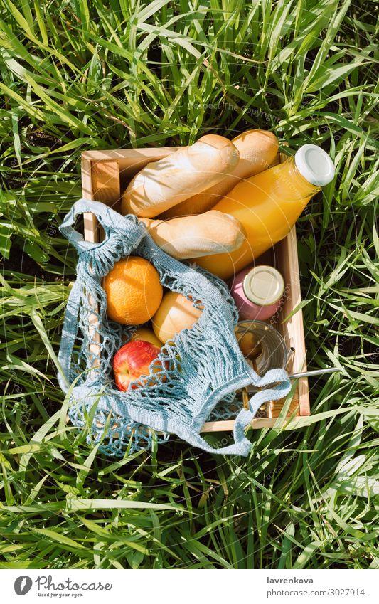 Verschiedene Früchte und kalte Getränke in einer Holzkiste Picknick Ökobeutel Baguette Brot Diät Glas Flasche Milchshake Saft orange Apfel Frucht