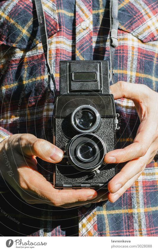 Nahaufnahme der Hände des Mannes, der eine Vintage-Kamera hält. retro einfangen Außenaufnahme Fotografie schießen alt kariertes Hemd gesichtslos Linse