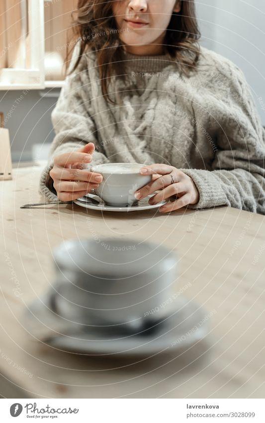 Frau hält einen Becher Latte mit einer leeren Tasse davor. Kaffee Tee Winter Herbst Pullover gesichtslos Einsamkeit gemütlich Wärme Verabredung Café Tisch