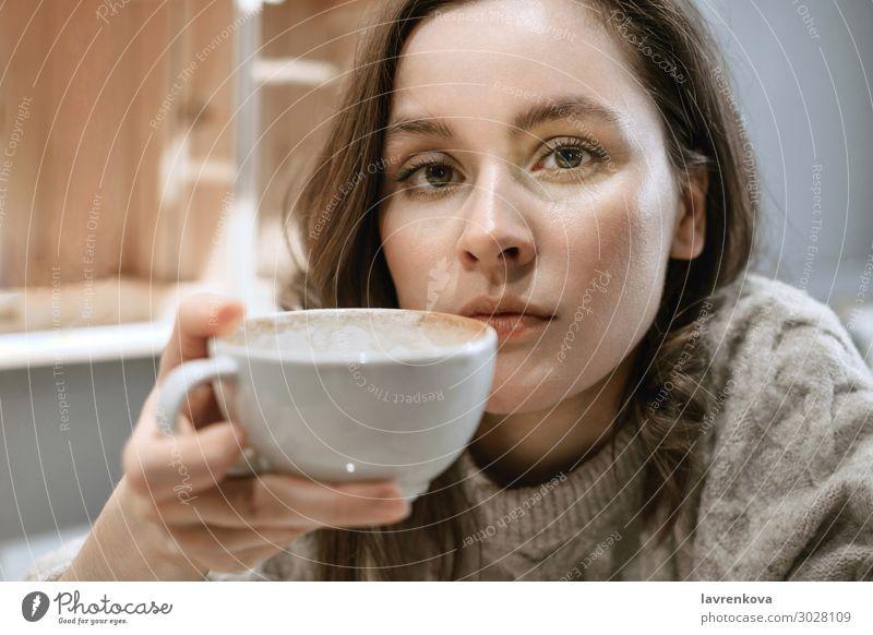 Junge erwachsene weiße Frau mit großer Tasse Latte Restaurant Pullover Jahreszeiten Getränk heiß Hygge Halt Tee Gesicht Becher Lifestyle Junge Frau Porträt