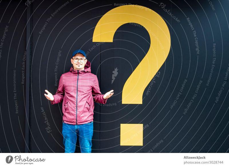 Junger Mann mit Regenjacke neben einem gelben Fragezeichen rot schwarz Denken nachdenklich Geschenk neu Überraschung Fragen Entscheidung 1 Mensch anonym unklar