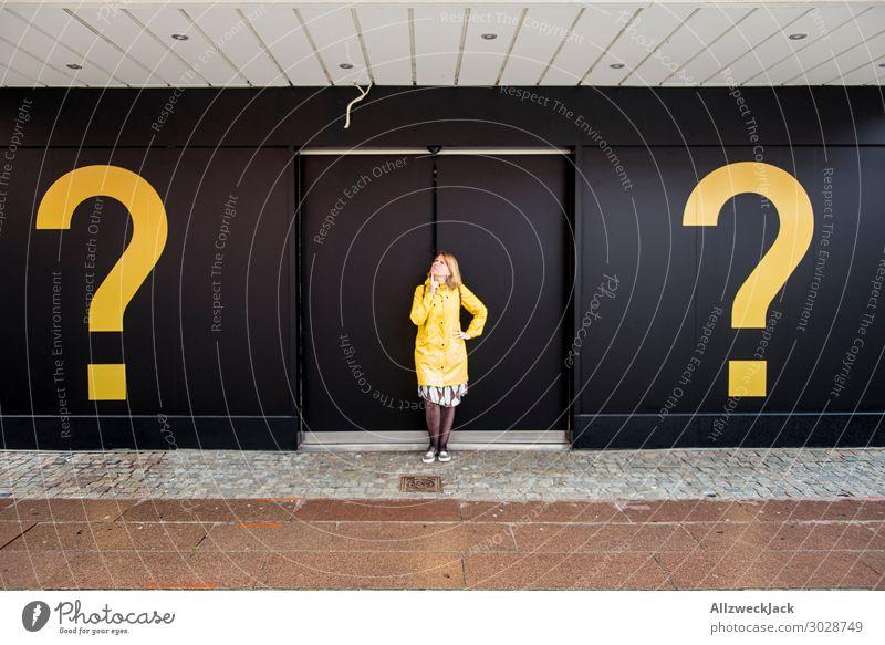 junge Frau mit gelber Regenjacke zwischen zwei Fragezichen Junge Frau schwarz Denken Fassade Tür nachdenklich neu Überraschung Fragen Entscheidung 1 Mensch