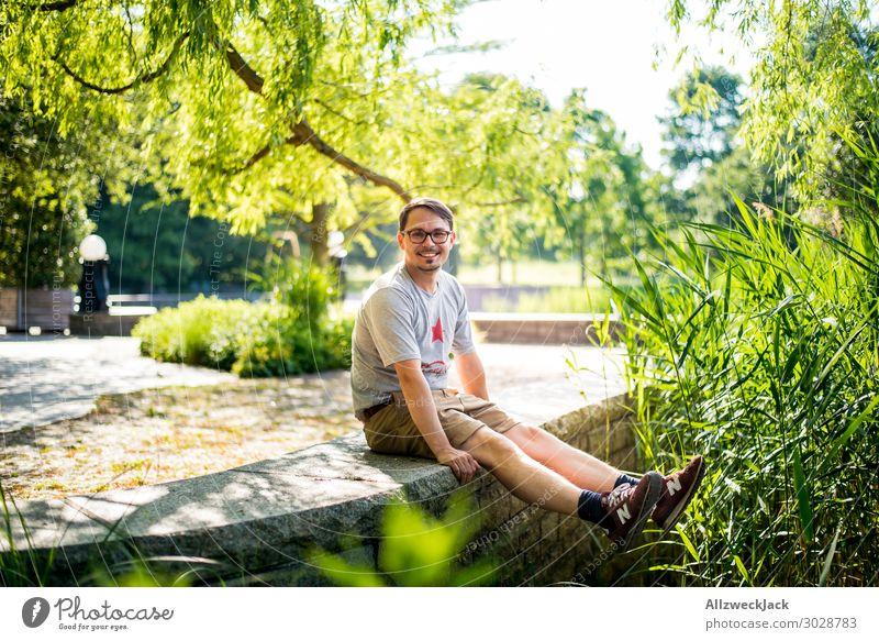 junger Mann sitzt auf einer Mauer und freut sich Schönes Wetter Wolkenloser Himmel Blauer Himmel grün Natur Baum Schilfrohr genießen Erholung Pause ausruhend
