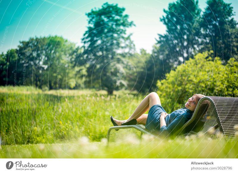 junge Frau sonnt isch auf einer Liege im Garten Schönes Wetter Wolkenloser Himmel Blauer Himmel grün Natur Wiese Rasen Sonnenbad genießen Erholung Pause