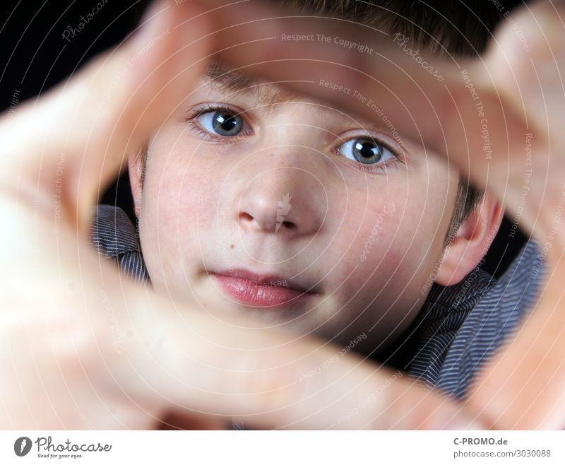 Junge schaut durch Rahmen seiner Finger Mensch maskulin Gesicht Auge 1 3-8 Jahre Kind Kindheit 8-13 Jahre Neugier Interesse Lächeln Farbfoto
