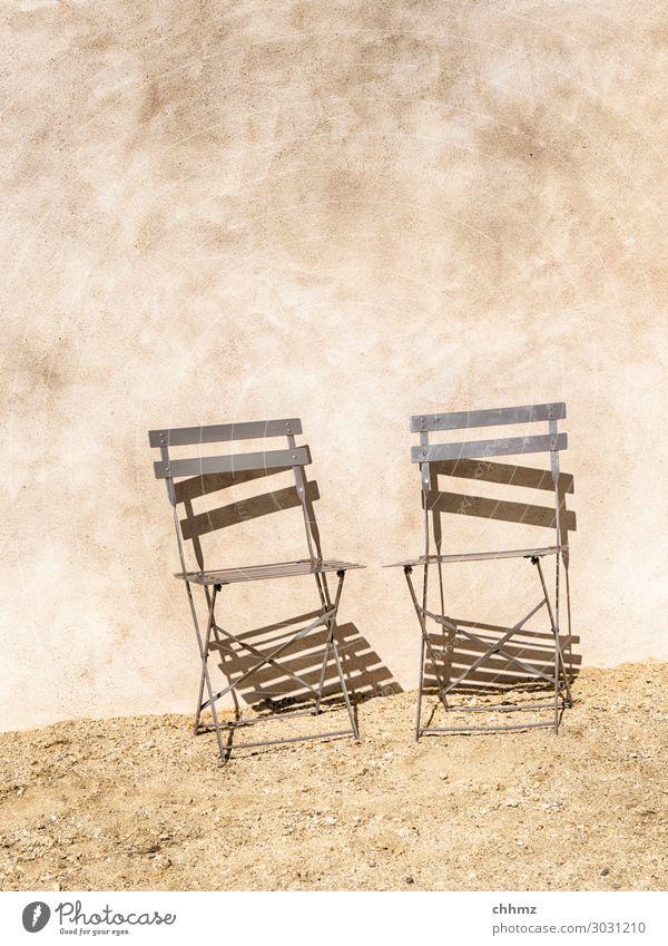 Zwei Stühle Stuhl Hauswand Putz Putzfassade metallstuhl Schatten Schattenspiel Wand Fassade Mauer Strukturen & Formen Textfreiraum oben Kies Schotter sonnig