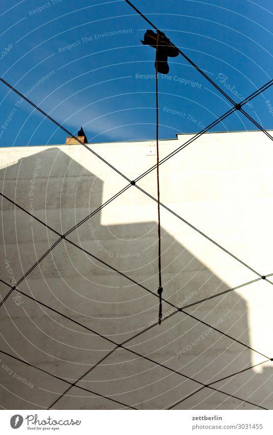 Schuhe, hängend Altbau Brandmauer Fassade Froschperspektive Haus Himmel Himmel (Jenseits) Blauer Himmel himmelblau hinten Hinterhof Hof Innenhof Stadtzentrum