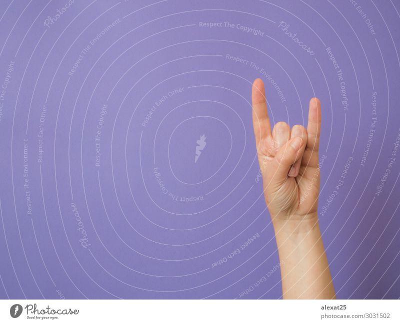 """Weibliche Hand zeigt Zeichen """"Teufel"""" auf violettem Hintergrund Musik Mensch Arme Finger Felsen Metall weiß Entwurf konzeptionell Textfreiraum böse Ausdruck"""