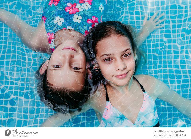 zwei schöne Teenagermädchen, die in einem Pool schwimmen. Lifestyle Freude Glück Erholung Schwimmbad Freizeit & Hobby Ferien & Urlaub & Reisen Sommer Sonne