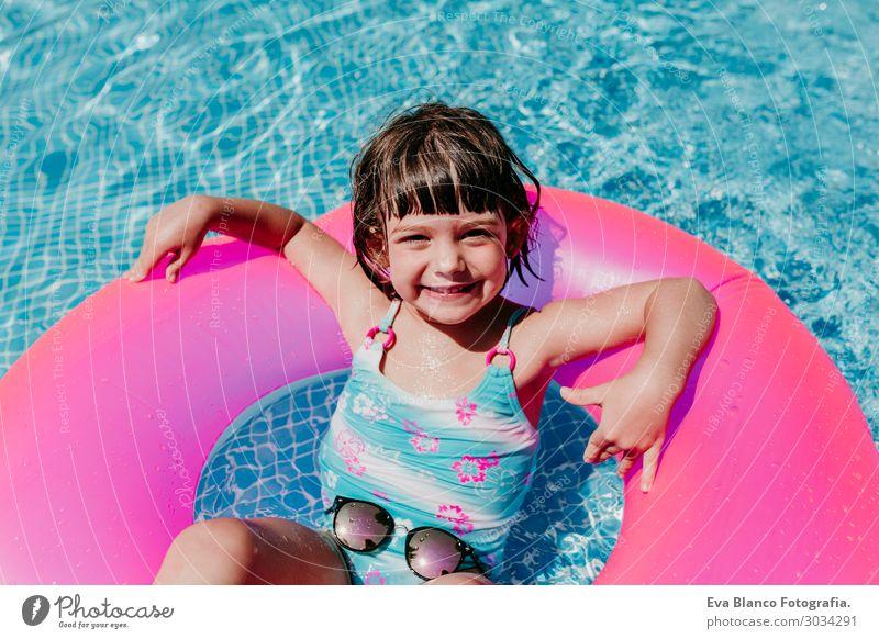 schönes Kind Mädchen, das auf rosa Donuts in einem Pool schwimmt. Lifestyle Freude Glück Erholung Schwimmbad Freizeit & Hobby Ferien & Urlaub & Reisen Sommer