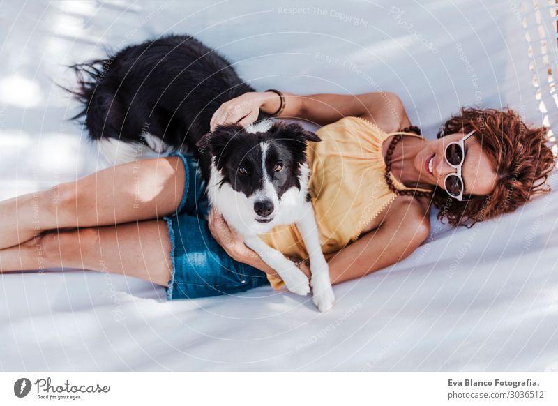 schöne Frau, die mit ihrem Hund auf der Hängematte liegt. Lifestyle Freude Glück Erholung Freizeit & Hobby Ferien & Urlaub & Reisen Sommer Garten feminin