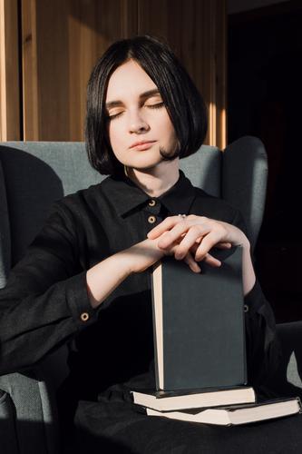 Frau auf einem Stuhl mit Büchern sitzend Buch Freizeitbekleidung Kaukasier gemütlich Kleid Finger Junge Frau Hand Freizeit & Hobby Halt heimwärts Hygge
