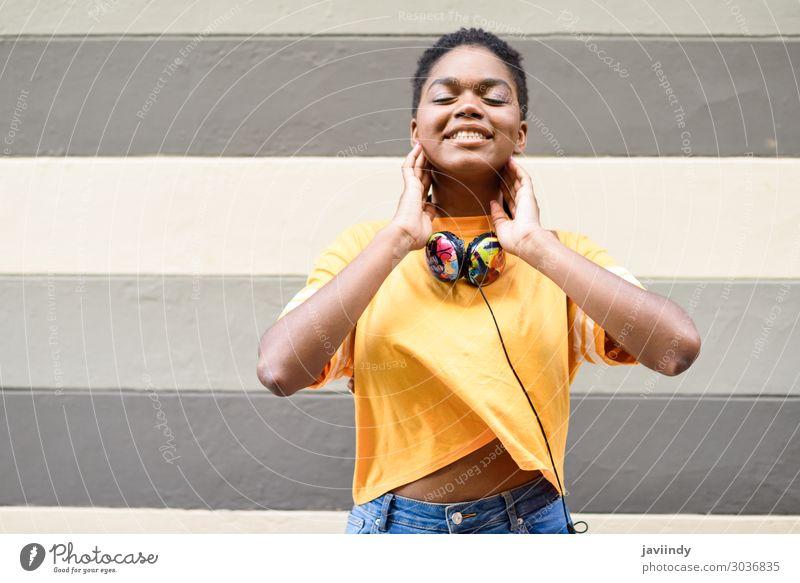 Glückliche afrikanische Frau lächelt an der Stadtmauer mit geschlossenen Augen. Lifestyle Stil schön Haare & Frisuren Gesicht Musik Headset Mensch feminin