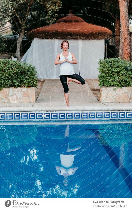 Frau, die Yoga am Swimmingpool macht. Yoga und Achtsamkeit Lifestyle schön Körper Erholung ruhig Meditation Spa Schwimmbad Freizeit & Hobby
