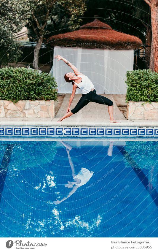 Frau, die Yoga am Swimmingpool macht. Yoga und Achtsamkeit Lifestyle schön Körper Erholung ruhig Meditation Spa Schwimmbad Ferien & Urlaub & Reisen Sommer Sonne