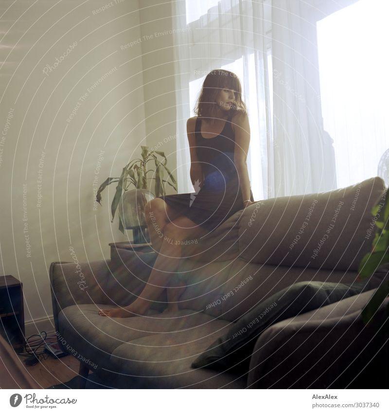 Junge Frau sitzt auf Couch im Wohnzimmer Lifestyle Stil schön Zufriedenheit Wohnung Möbel Sofa Jugendliche 18-30 Jahre Erwachsene Grünpflanze Fenster Kleid