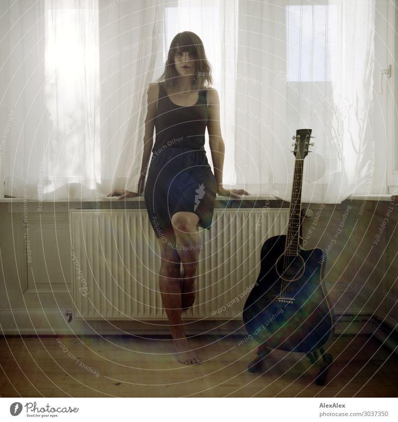 Junge Frau sitzt am Fenster neben Gitarre Jugendliche Stadt schön Freude 18-30 Jahre Lifestyle Erwachsene Stil außergewöhnlich Wohnung sitzen ästhetisch