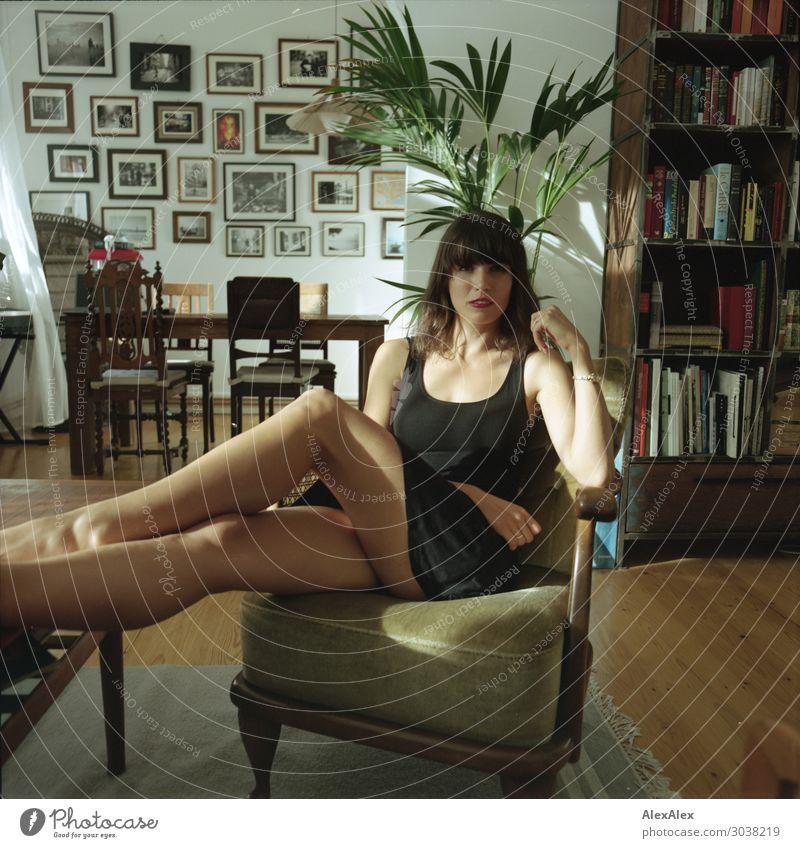 Junge Frau im Wohnzimmer auf einem Sessel Lifestyle elegant Stil schön Erholung Häusliches Leben Möbel Bücherregal Bilderrahmen Zimmerpflanze Jugendliche Beine