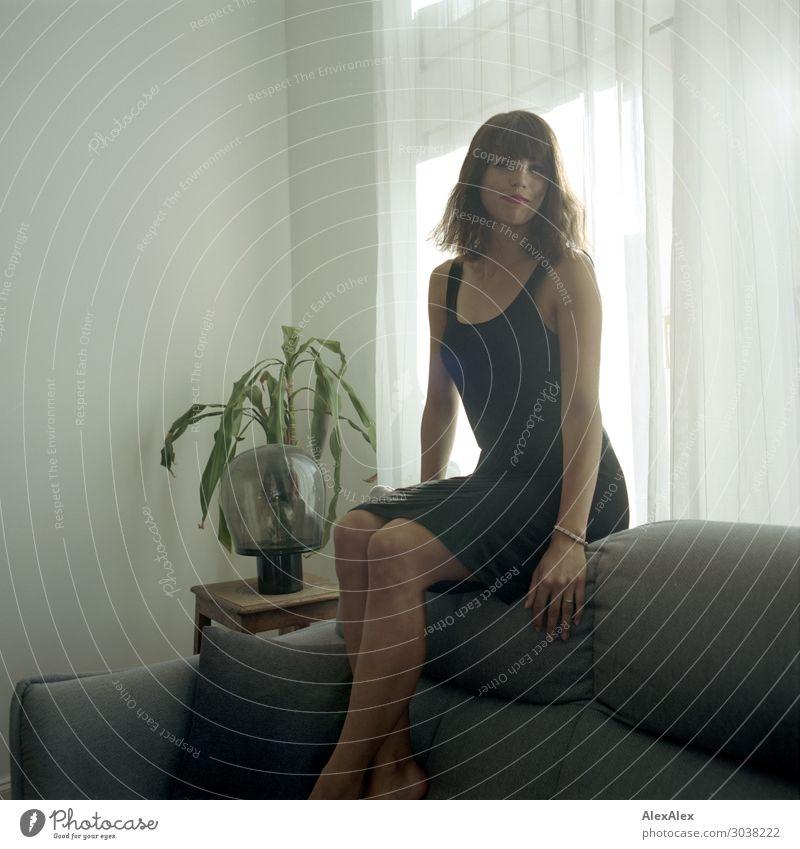 Junge Frau sitzt auf Couch im Wohnzimmer Jugendliche Stadt schön Freude 18-30 Jahre Lifestyle Erwachsene Leben Glück Stil Wohnung Lächeln sitzen ästhetisch