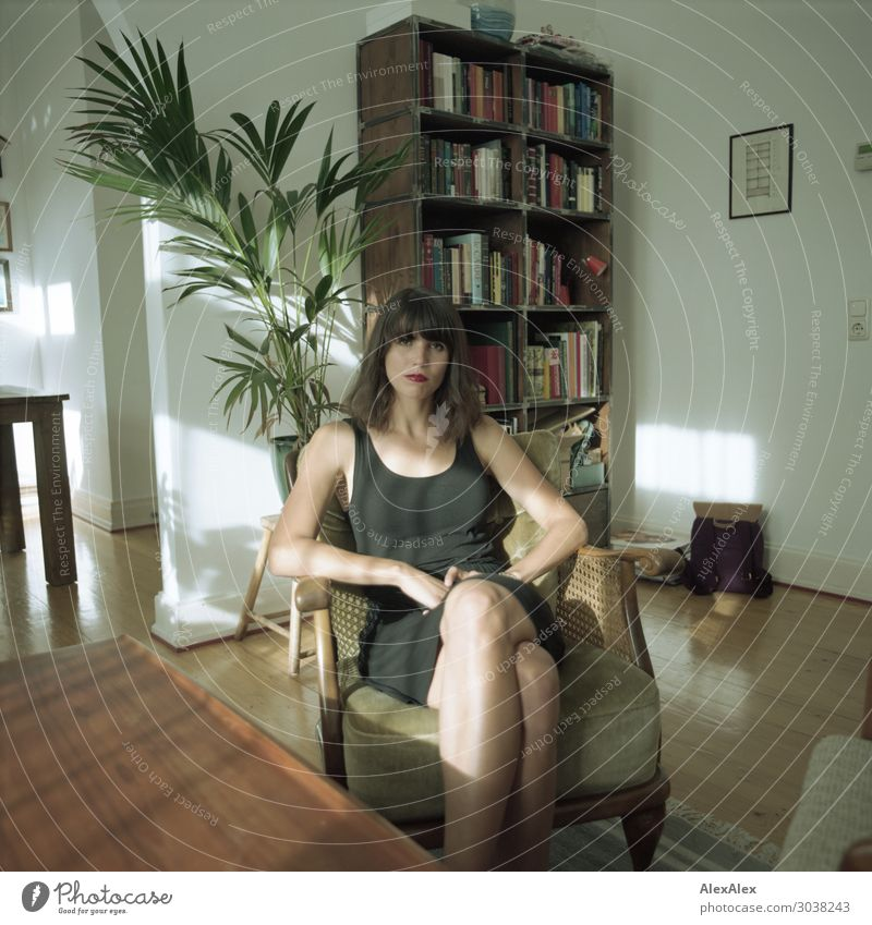 Frau sitzt im Wohnzimer am Tisch Jugendliche Junge Frau Stadt schön 18-30 Jahre Lifestyle Erwachsene Holz Stil Wohnung Zufriedenheit sitzen ästhetisch