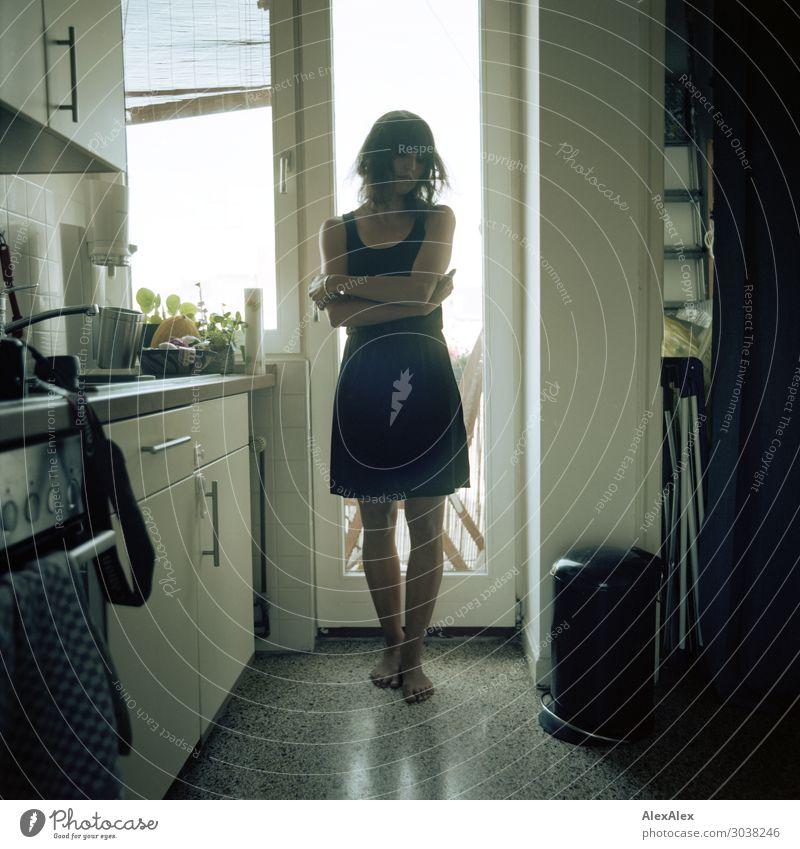 Gegenlichtportrait einer jungen Frau in der Küche Lebensmittel Ernährung Lifestyle Stil Freude Zufriedenheit Wohnung Junge Frau Jugendliche 18-30 Jahre