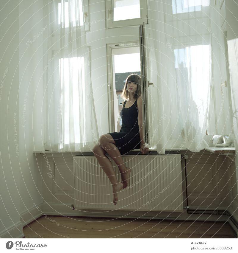 Junge Frau sitzt im Fenster Lifestyle Stil schön Zufriedenheit Wohnung Raum Heizkörper Parkett Jugendliche 18-30 Jahre Erwachsene Schönes Wetter Kleid Barfuß