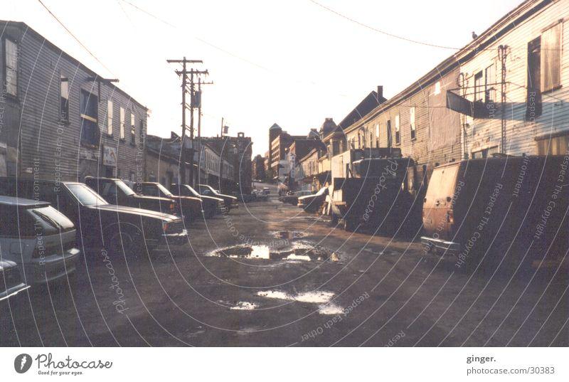 Seitenstraße Straße trist Maine Pfütze Hochspannungsleitung Haus Häuserzeile Schlagloch Ghetto analog Menschenleer Zentralperspektive schäbig Tag verfallen