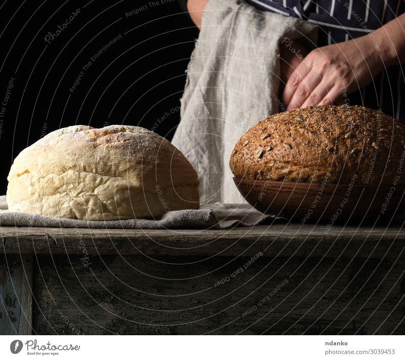 gebackenes Rundbrot auf einem Holztisch Brot Teller Tisch Küche Mensch Frau Erwachsene Arme Hand alt machen frisch braun gelb grau schwarz weiß Tradition