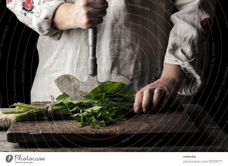 Frau schneidet grüne Blätter von frischem Sauerampfer. Gemüse Suppe Eintopf Kräuter & Gewürze Ernährung Vegetarische Ernährung Messer Tisch Küche Erwachsene