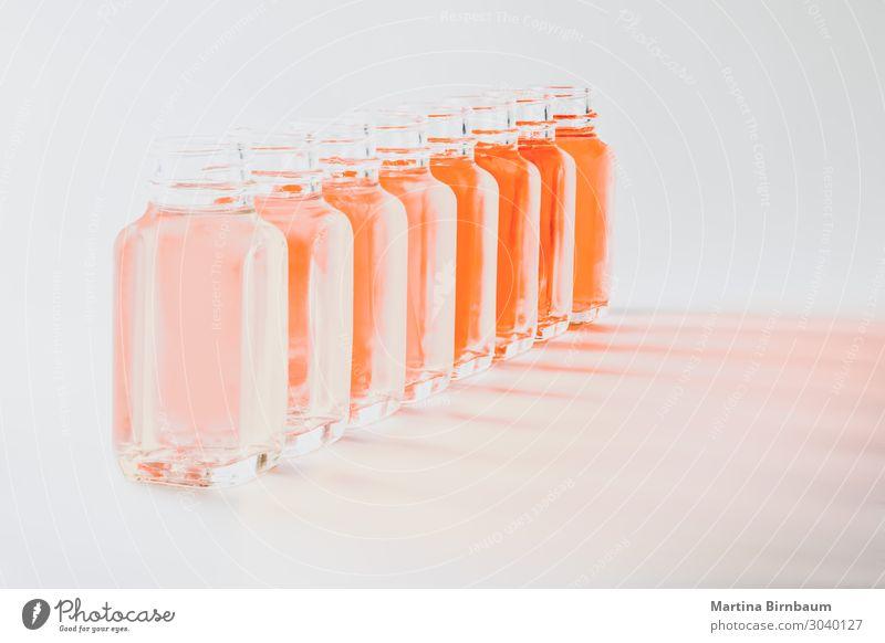 Flaschen mit korallenfarbenen Flüssigkeiten in verschiedenen Farbtönen Gemüse frisch nass braun rosa weiß Korallen vereinzelt lebend Hintergrund orange Palette