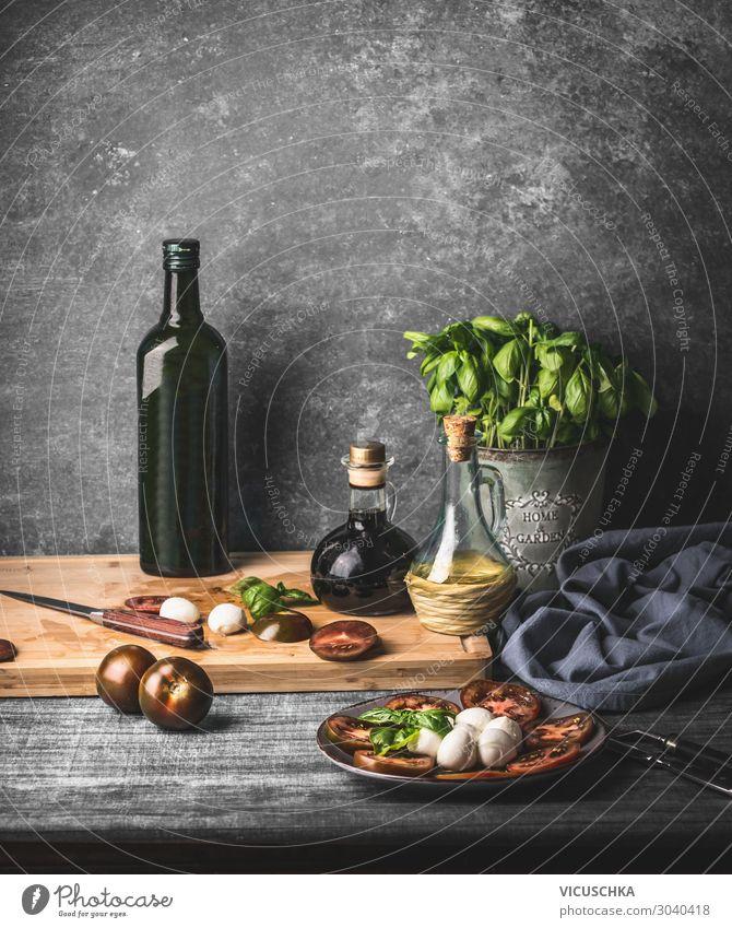 Stilleben mit italienischem Caprese-Salat, serviert auf rustikalem Tisch mit eingelegten Basilikum-Küchenkräutern und einer Flasche Olivenöl auf rustikalem Tisch mit Zutaten
