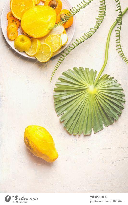 Ganze Papayafrucht auf weißem Tisch mit tropischen Blättern und Teller mit gelben, geschnittenen Früchten, Draufsicht. Sommerliches Essen. Gesunde Ernährung. Teller mit Frühstücksfrüchten. Platz zum Kopieren. Modern. Flach liegend