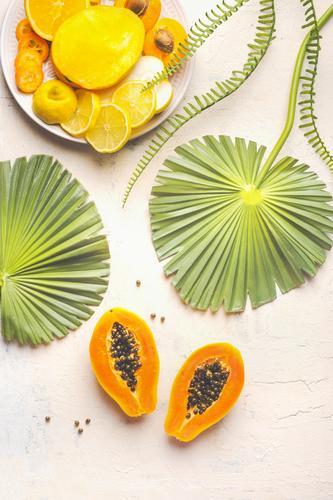 Halbierte reife Papayafrucht mit Samen auf weißem Tisch mit tropischen Blättern und Teller mit gelben geschnittenen Früchten, Draufsicht. Sommerliches Essen. Gesunde Ernährung. Frühstücks-Früchteteller. Modern. Raum kopieren