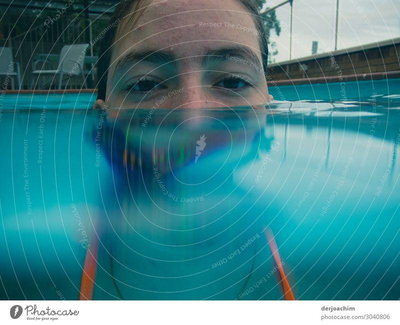 Halb unter Wasser ist das Gesicht eines Mädchens im Pool. Man sieht nur die Augen und die Stirn. Freude Erholung Sommer feminin Junge Frau Jugendliche