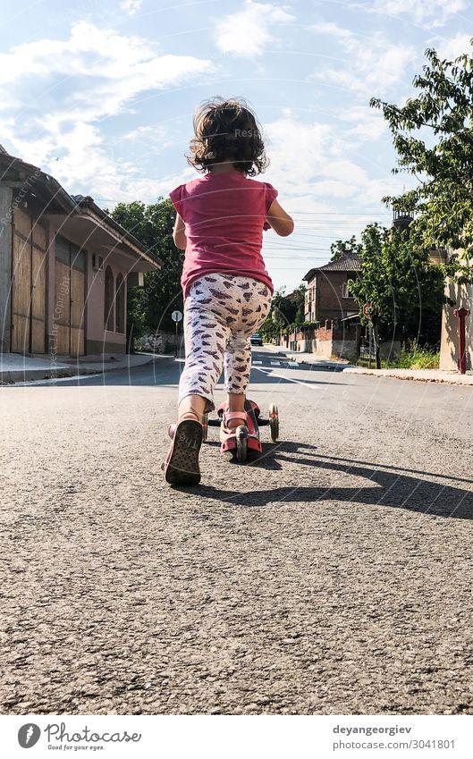 Kleines Mädchen spielt mit dem Roller auf der Straße. Freude Leben Freizeit & Hobby Spielen Sonne Sport Bewegung niedlich Tretroller Kind Frühling Großstadt