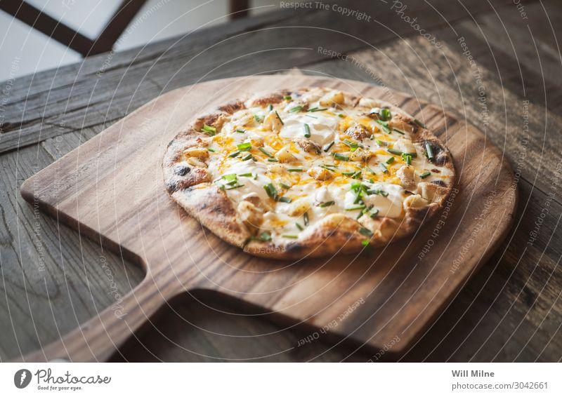 Eine frisch gebackene Pizza auf einem Holztablett. Lebensmittel Käse Teigwaren Backwaren Essen Mittagessen Fastfood Italienische Küche Restaurant Auflauf