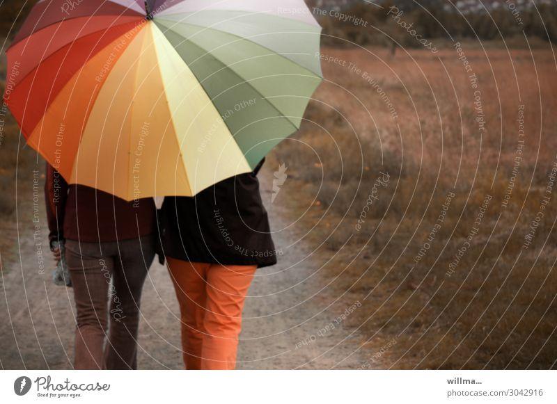 Zwei Personen spazieren mit einem großen bunten Regnschirm durch die Natur Menschen zwei Personen Regenschirm wandern Regenwetter Spaziergang Freizeit & Hobby