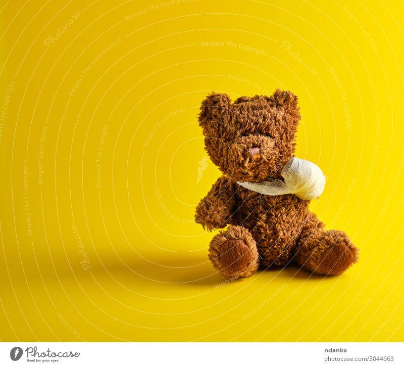 brauner Teddybär mit einer bandagierten Pfote sitzend Freude Behandlung Krankheit Medikament Kind Krankenhaus Kindheit Spielzeug Puppe klein lustig niedlich