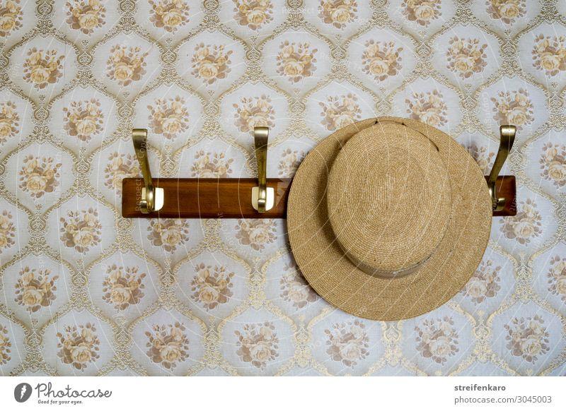 Strohhut hängt an Garderobe vor gemusterter Tapete Wohnung Kleiderständer Kleiderhaken ausgehen Bekleidung Hut Holz Feste & Feiern Ferien & Urlaub & Reisen alt
