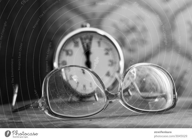 Der Blick durch die alte, verschmutzte Brille auf den alten Wecker im Hintergrund zeigte nur umso deutlicher, dass es bereits fünf vor zwölf war Wohnung Raum