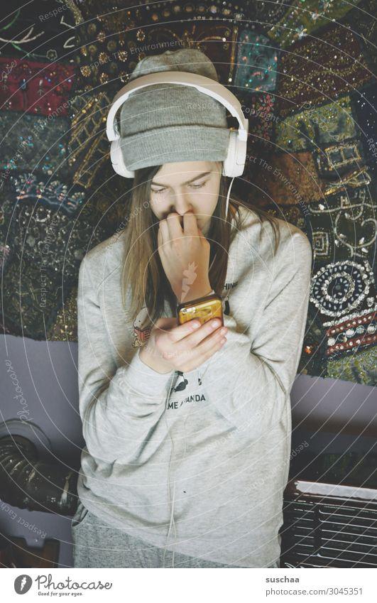 jugendliche mit kopfhörern und mütze steht an einer zimmerwand mit ofen im hintergrund und schaut auf ihr smartphone Teenager Jugendliche Mädchen